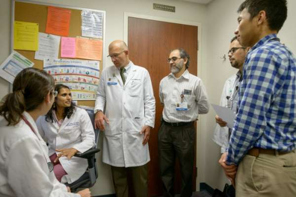 Borna Mehrad, M.D., chief of the UF College of Medicine's division of pulmonary, critical care and sleep medicine, meets with members of UF Health's interstitial lung disease team